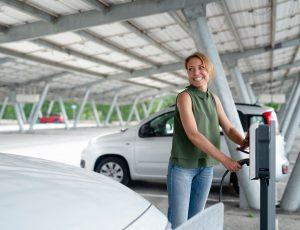 Woman charging electric car