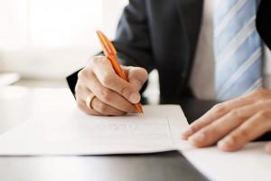Man writing note with orange pen